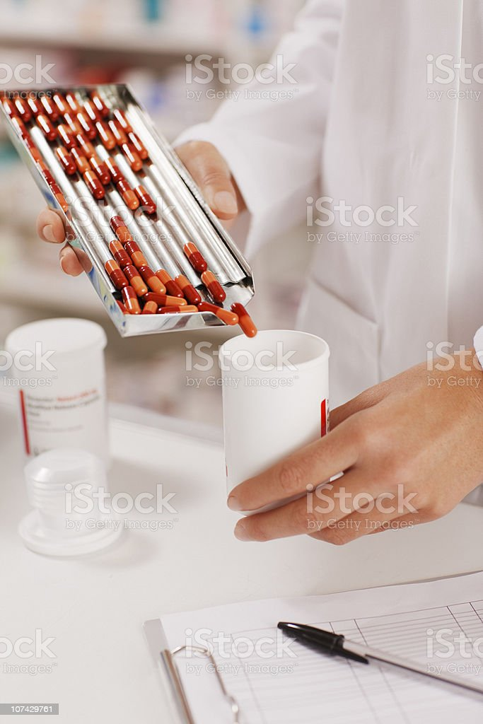 Pharmacist in drug store measuring pills into bottle stock photo
