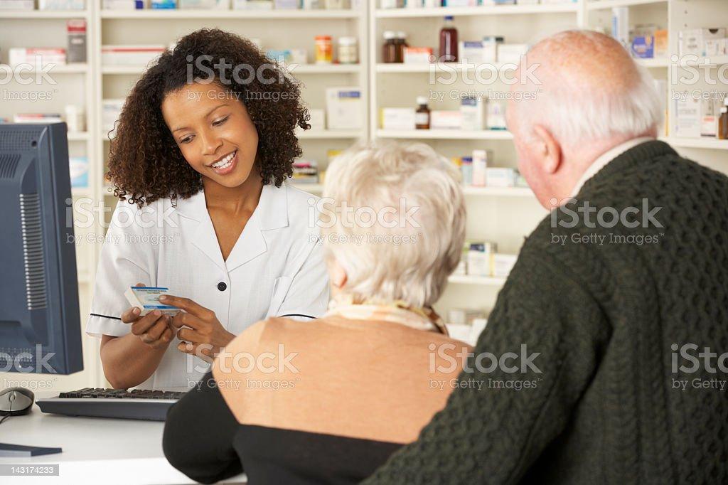 Pharmacist in pharmacy with senior couple stock photo