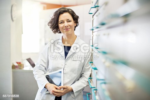 istock Pharmacist leaning to a medicine shelf with digital tablet 537316838