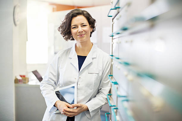 Pharmacist leaning to a medicine shelf with digital tablet stock photo