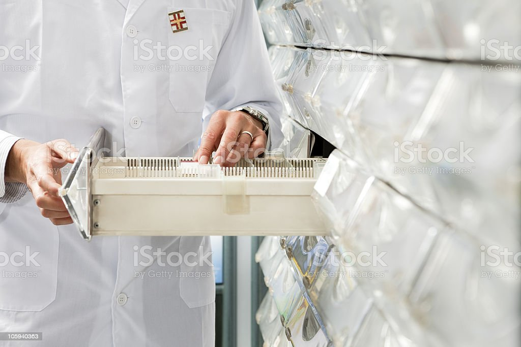 Pharmacist locating and putting away medicine stock photo