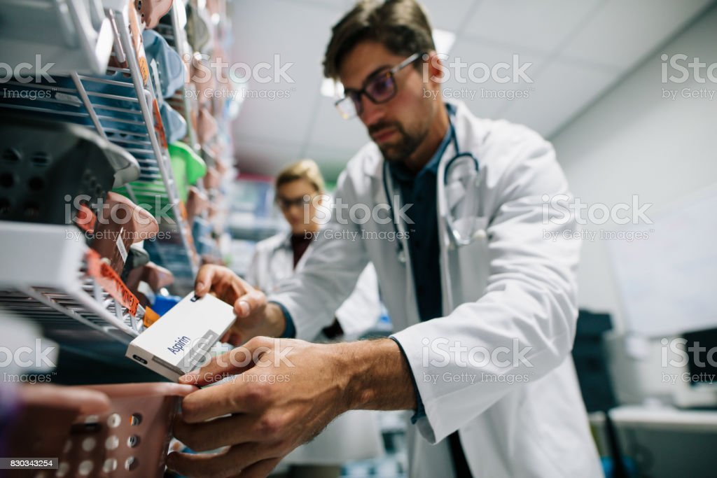 Pharmacist looking for a drug on shelf stock photo