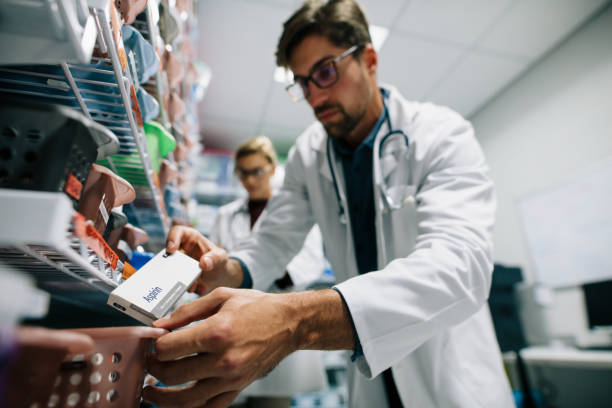 pharmacist looking for a drug on shelf - medical supplies stock photos and pictures