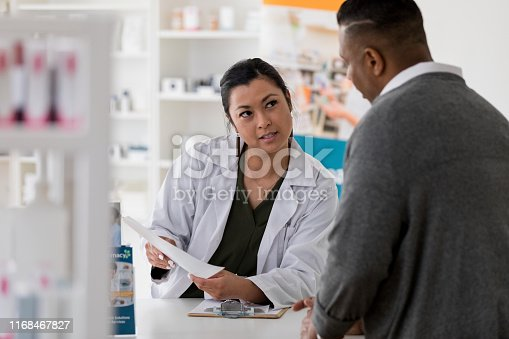 After explaining the insurance costs for the medication, the mid adult pharmacist looks at the customer to confirm his understanding of the information.