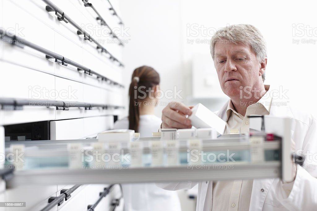 Pharmacist on duty Portrait of mature pharmacist searching for medicines in shelf with colleague in background 40-49 Years Stock Photo