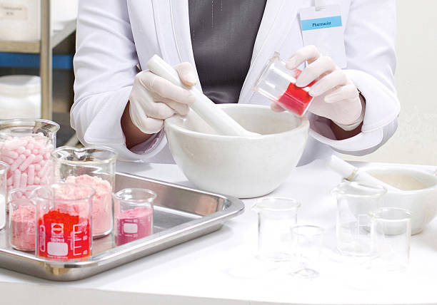 pharmacist preparing medication with mortar stock photo