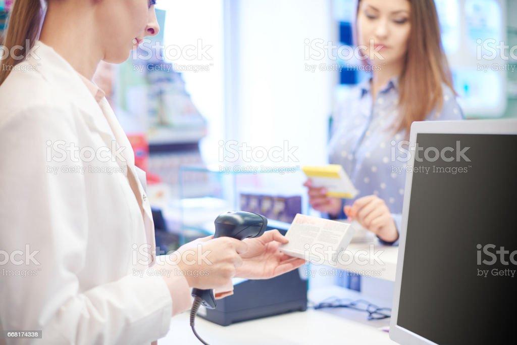 Pharmacist scanning pill box stock photo