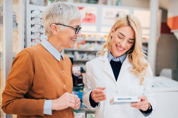 Pharmacist selling a medicine to a mature customer stock photo