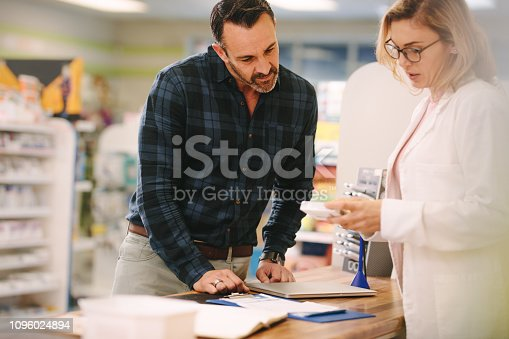 Female pharmacist showing medicine to male customer in pharmacy. Chemist suggesting medical drug to buyer in pharmacy drugstore.