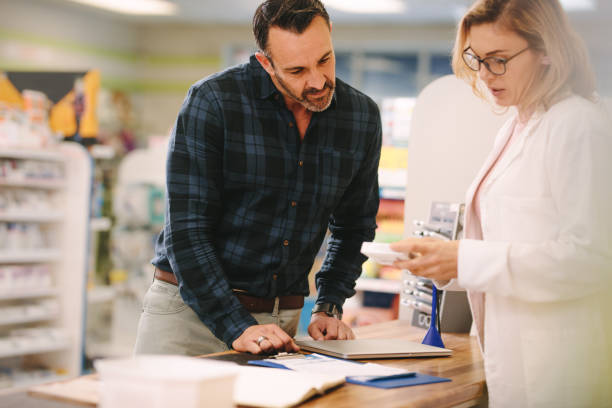 pharmacist showing medicine to customer in pharmacy - farmácia imagens e fotografias de stock