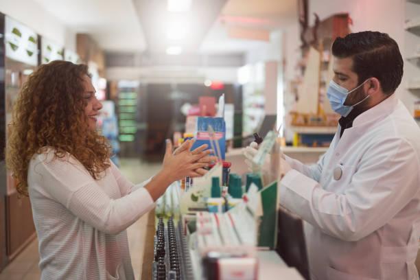 Apotheker drückt Handdesinfektionsmittel an den Kunden – Foto