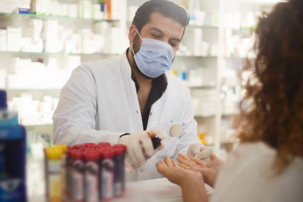 pharmacist squeezes hand sanitizer to the customer pharmacist squeezes hand sanitizer to the customer pharmacy stock pictures, royalty-free photos & images