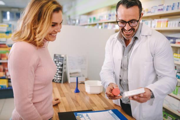 farmacéutico, sugiriendo drogas médicas al comprador - receta instrucciones fotografías e imágenes de stock