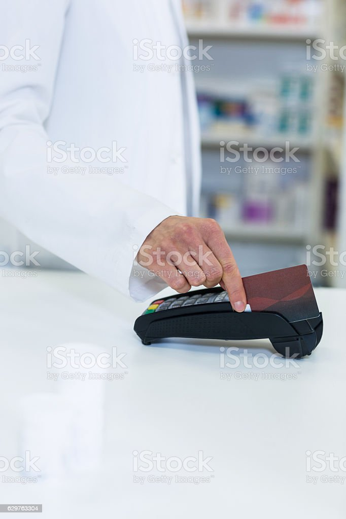 Pharmacist swiping card through payment terminal stock photo