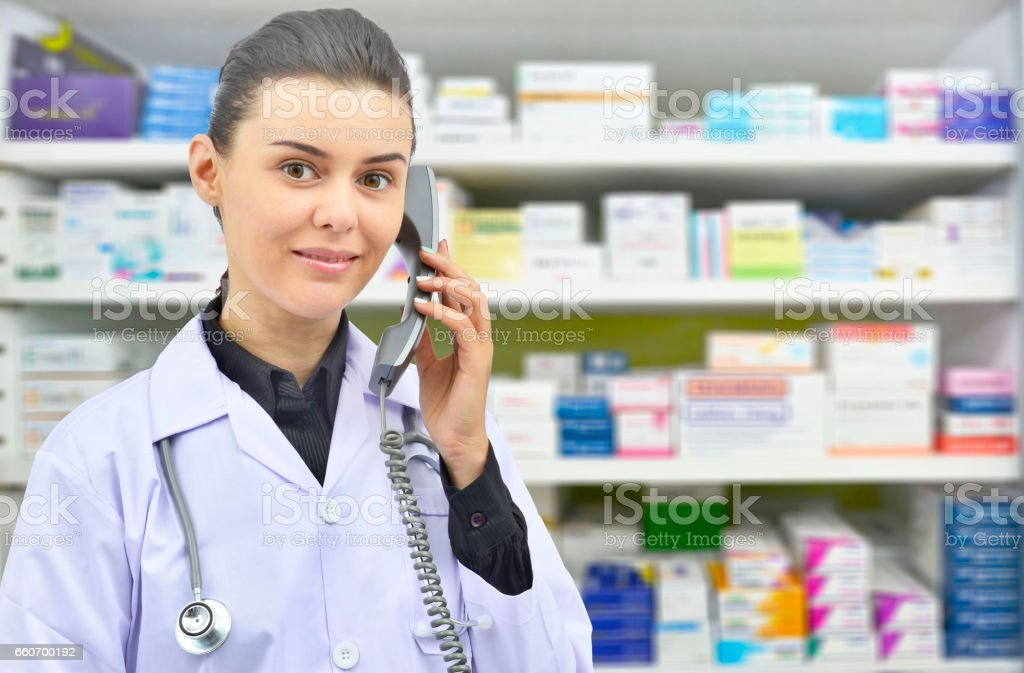 Pharmacist Talking to Someone on Phone in drugstore. stock photo