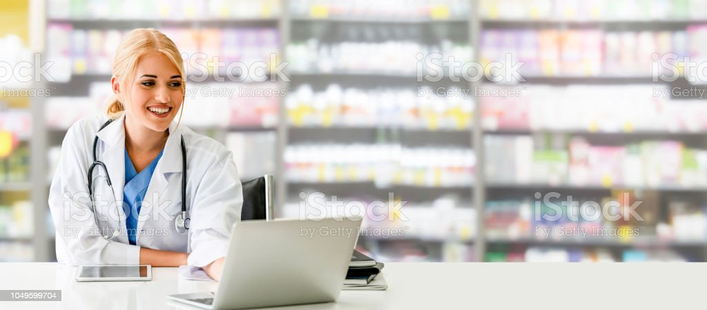 Pharmacist using laptop computer at pharmacy. stock photo