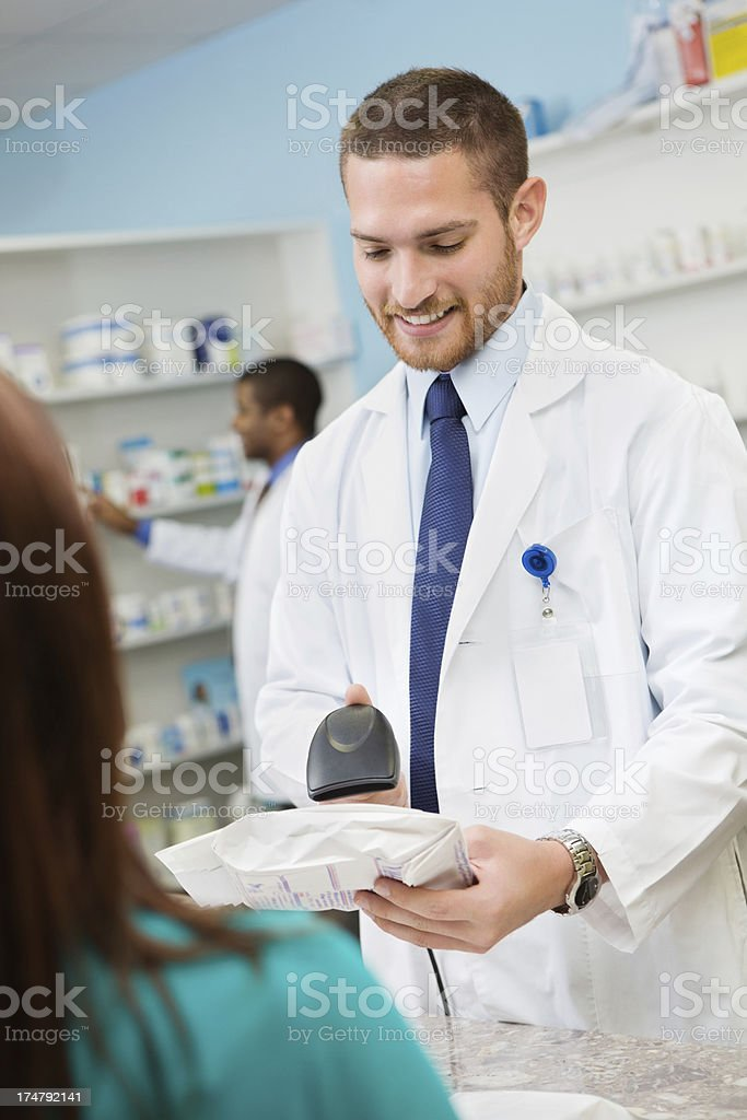 Pharmacist using scanner to check out presciption for pharmacy customer stock photo