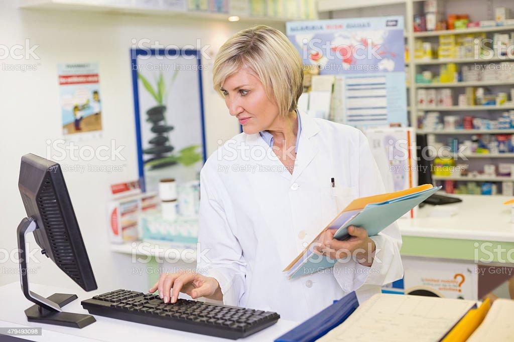 Pharmacist using the computer stock photo