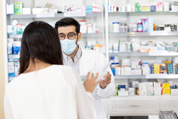 Pharmacist wearing protective hygienic mask and making drug recommendations in modern pharmacy stock photo