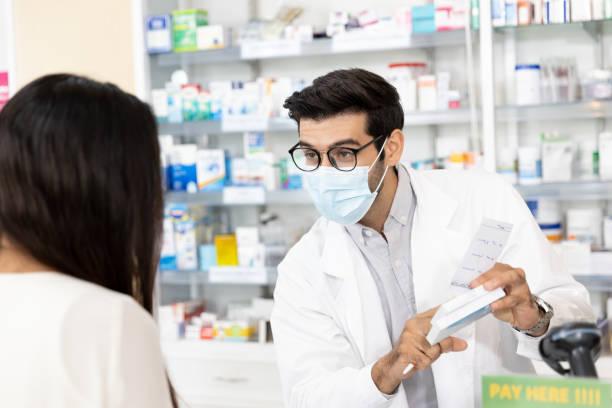 보호 위생 마스크를 착용하고 현대 약국에서 약물 권장 사항을 만드는 약사 - 약사 뉴스 사진 이미지