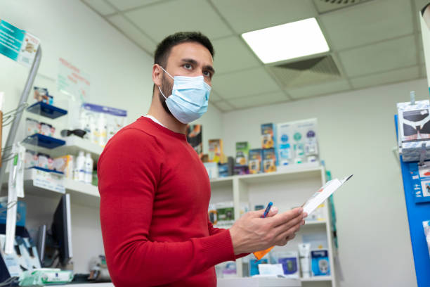 pharmacist wearing protective surgical mask in the shop - essential workers stock pictures, royalty-free photos & images