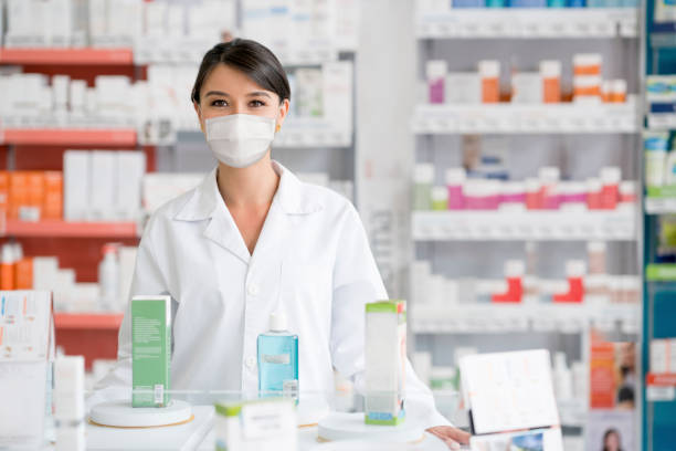 Pharmacist working at the drugstore and wearing a facemask during the COVID-19 pandemic stock photo