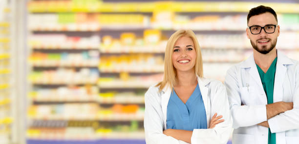 Pharmacist working with colleague in pharmacy. stock photo