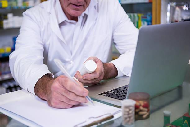 pharmacist writing prescriptions for medicines - lieblingsrezepte stock-fotos und bilder