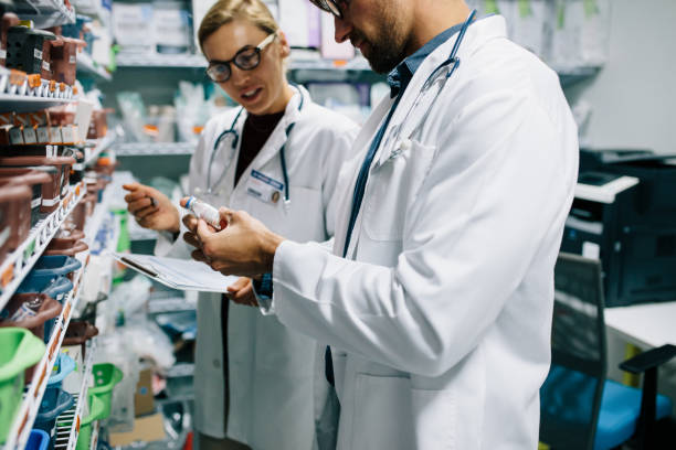 Pharmacists checking inventory at pharmacy stock photo
