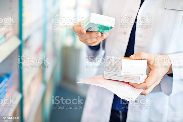 Pharmacists Hands Taking Medicines From Shelf Stock Photo - Download Image Now