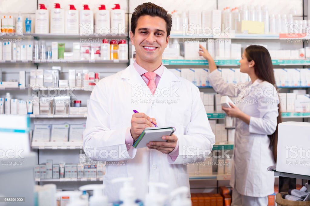 pharmacists  posing in drugstore stock photo