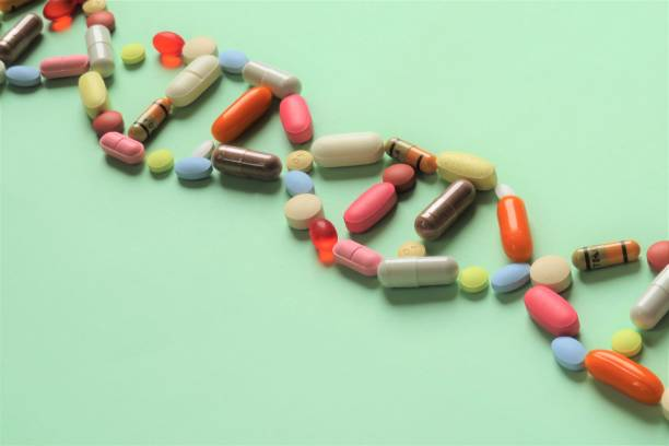 Pharmacogenetics Horizontal image of prescription capsules and tablets of various shapes and colors arranged diagonally in the shape of DNA to represent pharmacogenetics.  Green background. gene therapy stock pictures, royalty-free photos & images