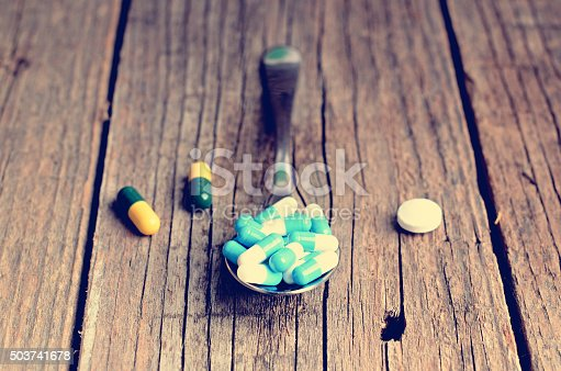 istock Pharmacy background. Full spoon of pills on a wooden table. 503741678