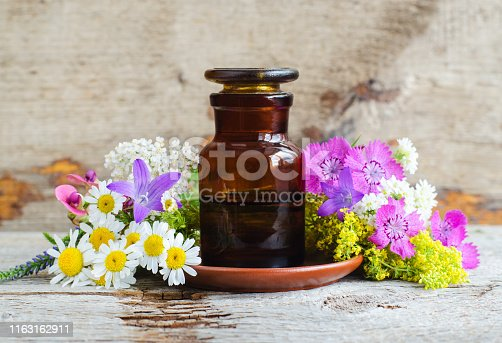 istock Pharmacy bottle and various wild flowers. Herbal tincture (essential oil, infusion, extract, syrup, compound). Old wooden background. Aromatherapy, spa and herbal medicine concept. Copy space. 1163162911