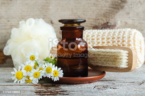istock Pharmacy bottle with roman chamomile essential oil (extract, tincture, infusion) and wooden brush. Old wooden background. Aromatherapy, spa and herbal medicine concept. Copy space. 1174419953
