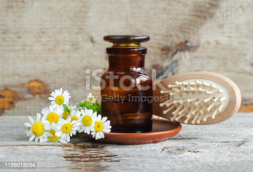 istock Pharmacy bottle with roman chamomile essential oil (extract, tincture, infusion) and wooden hair brush. Old wooden background. Aromatherapy, natural hair care, spa, herbal medicine concept. Copy space 1159018254