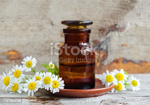 istock Pharmacy bottle with roman chamomile essential oil (extract, tincture, infusion). Old wooden background. Aromatherapy, spa and herbal medicine concept. Copy space. 1157354296