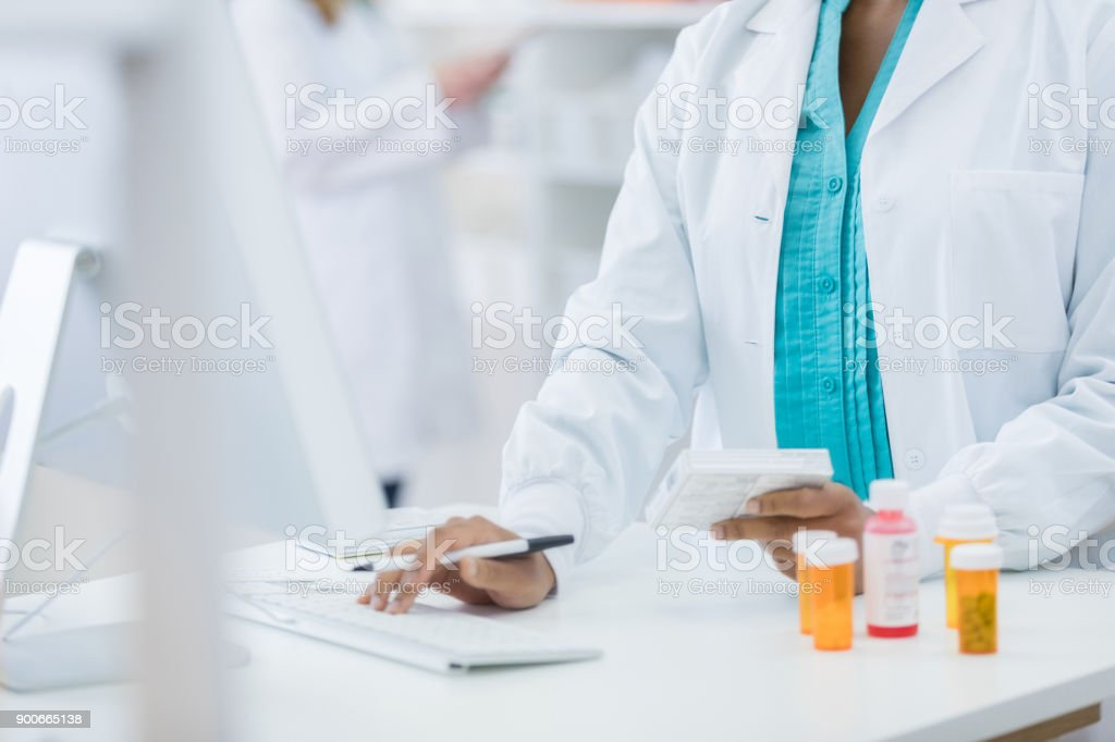Pharmacy checking computer while filling prescription for customer stock photo