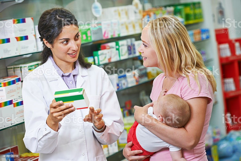 Pharmacy chemist, mother and child in drugstore​​​ foto