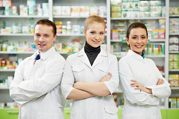 Pharmacy chemist team women and man in drugstore stock photo