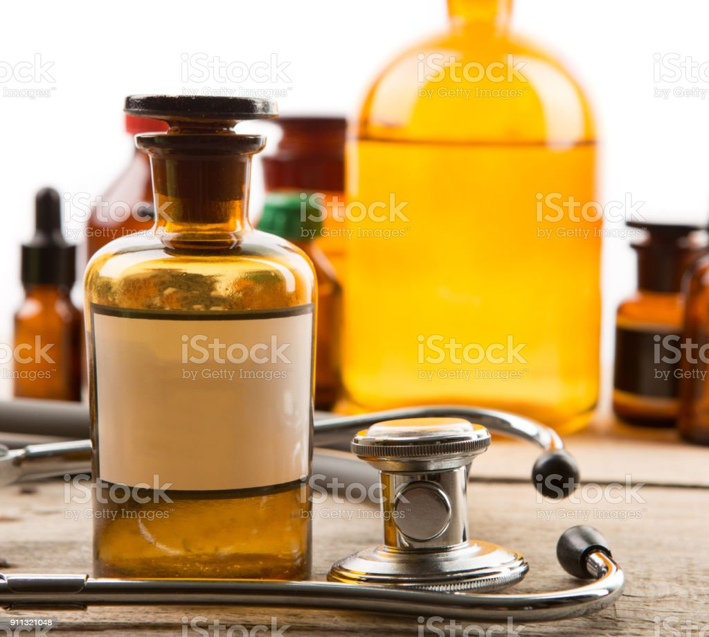 Pharmacy container with blank label and vintage medical bottles on the background stock photo