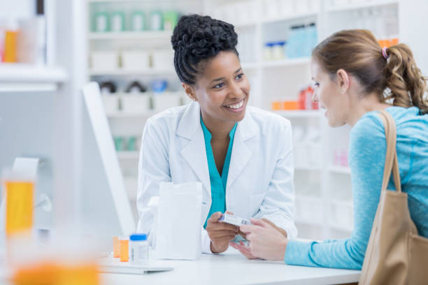 Pharmacy customer asks pharmacist question about medication stock photo