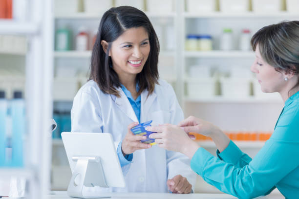 Pharmacy customer talks with pharmacist about medication stock photo