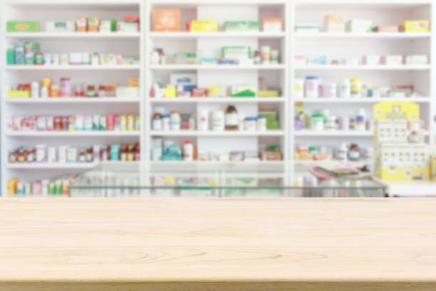 pharmacy drugstore counter table with blur abstract backbround with medicine and healthcare product on shelves - pharmacy stock pictures, royalty-free photos & images