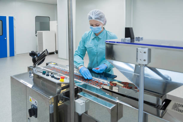 pharmacy industry woman worker in protective clothing operating production of tablets in sterile working conditions - pharma stock photos and pictures