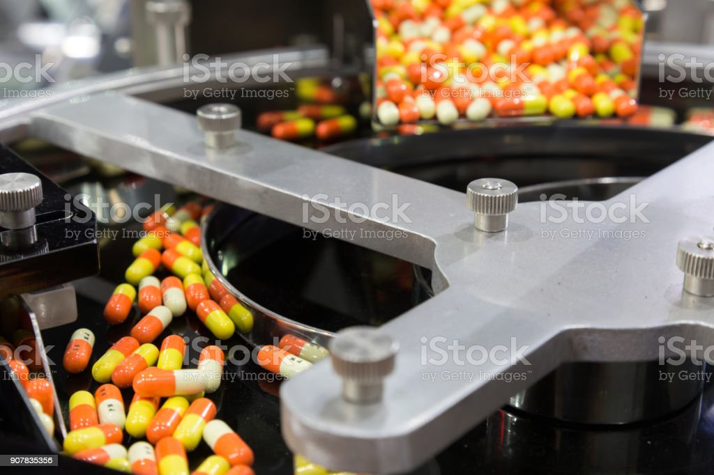 pharmacy medicine capsule pill in production line at medical factory. selective focus. stock photo