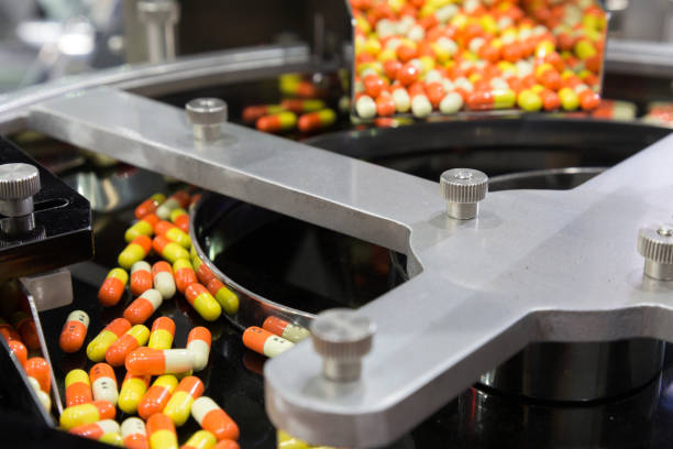 pharmacy medicine capsule pill in production line at medical factory. selective focus. - pharmaceutical factory stock pictures, royalty-free photos & images