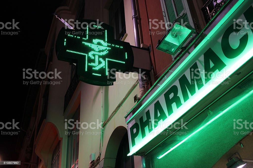 Pharmacy Neon Green Cross Sign at night stock photo