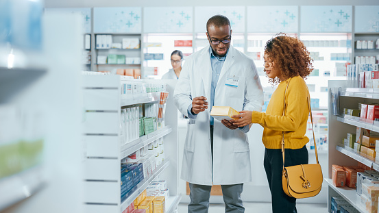 Pharmacy: Professional Black Pharmacist Helping Beautiful Latin Female Customer with Medicine Recommendation, Advice, Talking. Drugstore with Full of Drugs, Pills, Health Care, Beauty Product Packages