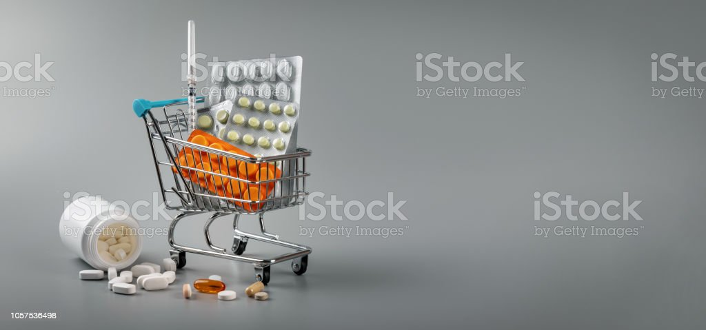pharmacy - shopping cart with pills on gray background with copy space stock photo